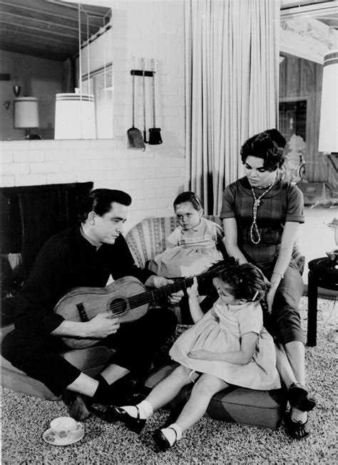 Johnny Cash holds a guitar as his first wife Vivian